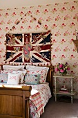 Wooden sleigh bed against floral wallpaper below Union Flag hanging on wall in traditional bedroom