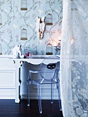 Designer acrylic chair and porcelain horse's head on a dressing table in front of floral wallpaper; romantic voile curtain in the foreground
