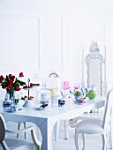Antique style white upholstered chairs at a romantic white table laid with pastel china, cake stand and glass covers