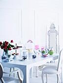 Antikisierende weiße Polsterstühle an romantisch weiss gedecktem Tisch mit pastellfarbenem Porzellan, Konfekt-Etagere und Glashauben