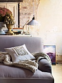 Cushion and knitted blanket on sofa with lilac upholstery in front of vintage pendant lamp and exposed brickwork of wall with crumbling plaster and peeling paint