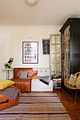 Framed ABC poster above 70s cushion chairs and striped, woven rug in front of large, vintage display cabinet