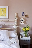 Bed with white bed linen and DIY headboard of birch branches with nesting box on wall. DIY grey bedside table with white, wooden breakfast tray.