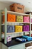 Colourful storage baskets with handles on shelves on top of country-house-style base cabinet