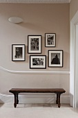 An old wooden bench in a hallway underneath framed black and white photographic prints