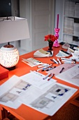 Orange work desk with pens and markers; at the edge a lighted table lamp, roses and a pink candle stick