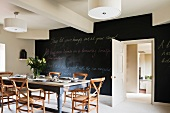 Dining room with black wall painted with blackboard paint