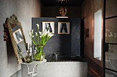 Concrete bath lined with small black ceramic tiles and partition wall in Moroccan home