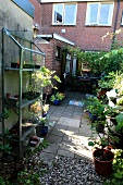 Allotment ambiance with plant nursery in front of paved and gravel terrace area of house with exposed brickwork and summery vintage character