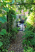 Simple swing on thick branch in small, narrow back garden edged by greenery with gravel path leading to paved terrace of house; peaceful, summery atmosphere