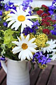 Summery bouquet of ox-eye daisies and blue, red and yellow flowers in pale grey ceramic jug on wooden garden table