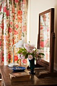 Antique wooden chest of drawers with swivelling mirror on top next to delicate posy of dog roses and small stack of books in a feminine ambiance