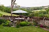 Idyllic seating area on corner terrace against stone garden wall with table, chairs and parasol and view across rolling English landscape in background
