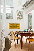 Wooden table with yellow metal chairs, sign with a quote from Bazon Brock and works by Eduarda Paolozzi in the kitichen