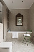 Framed mirror over a bathtub in a bathroom with mosaic tiles; green chair with bath towel