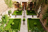 View of a symmetrically designed courtyard with a statue, boxwood hedge and paved walkway