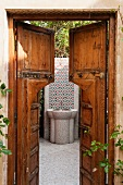 View through an open wooden door of a tiled hand basin in a courtyard
