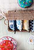 Pillow madness - ethnic cushion next to a basket with pillows on a striped surface