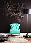 50's style turquoise armchair between modern floor lamps and upholstered ottoman in front of a black wall