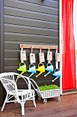 White rattan chair and retro style flower wagon cart in front of a black wall with colorful watering cans hanging on wall hooks
