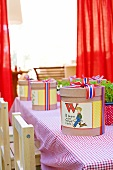 Beautifully packed boxes with large labels decorated with a child's theme on a children's table with checked tablecloth