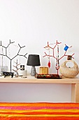 Decorative trees hanging with ornaments next to vintage table lamps and a wicker basket