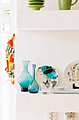 Blue glass vases and painted china plates on white shelves