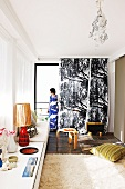 Curtain with black and white tree motif; collection of vintage objet on sideboard in foreground