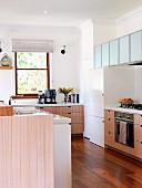 Fitted kitchen with pale, varnished wooden doors, frosted glass wall units and exotic-wood parquet floor
