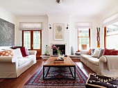 Pale sofas with scatter cushions and retro table on Oriental carpet in bright living room