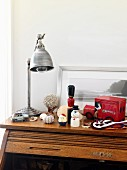 Industrial-style table lamp and toy ornaments on top surface of roll-top desk