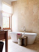 Warm shades of stone in bright bathroom with free-standing bathtub