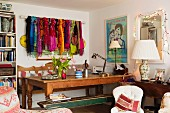 Wooden bench and oak table in corner of room next to full bookcase and collection of colourful scarves draped over curtain rod on wall; feminine atmosphere with fairy lights around mirror and china table lamp
