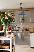 Fitted kitchen cupboards with various kitchen appliances on worksurface behind splendid bouquet of lilies on white-painted, narrow table