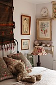 Corner of feminine bedroom with framed pictures and patterned china on wall bracket behind nostalgic bedside lamp on wooden chair; cuddly teddy bear waiting on cosy bed