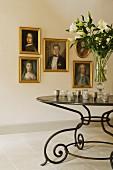 Historische Ölportraits mit Goldrahmen an weisser Wand; im Vordergrund ein schmiedeeiserner, schwarzer Tisch