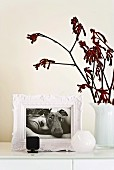 Romantic white picture frame with black and white photograph of dog and woman and plain, white frosted vase on white-painted cupboard element; red twigs add a splash of colour
