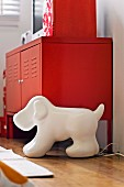 Red metal sideboard behind lamp in shape of stylised dog