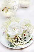 White roses and elder flowers on a place setting with a cup