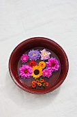 Assorted flowers (dahlia, zinnias, asters, sunflowers) in an old bowl with water