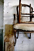 Antique, dilapidated chairs hanging on whitewashed brick wall