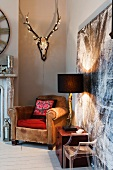 Fairy lights adorn a mounted stag head with antlers on wall above vintage leather armchair