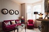 Raspberry coloured velvet furniture in living room with Graham and Green porthole wall mirrors