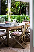 Garden porch with vintage wooden furniture in sunlight; in the background a white garden fence with a hedge