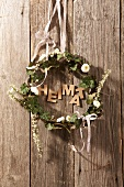 Wreath made of ivy and daisies and the word 'home'