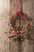 Wreath made from dried branches with pink forget me nots and carnations