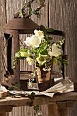 Strauss aus weissen Frühlingsblumen vor einer rostigen Laterne