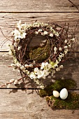 Wreath made of pussy willow and fruit blossom, moss and Easter eggs on a wooden surface