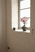 A branch with red berries in a vase on a window ledge