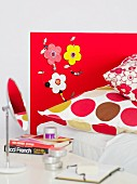 Artistic, 70s-style headboard with flowers, wooden beads and matching pillow covers on bed; tabletop mirror and French literature on bedside table